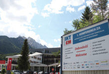 Welcoming jumbo banner. On the left there is Conference's Venue Ramada Resort hotel and beautiful Alps